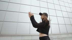 Girl dancer in black performs modern hip-hop dance, contemporary freestyle, urban environment