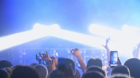 People at music concert, jumping clap hands strobe flashing lights, dancing fans