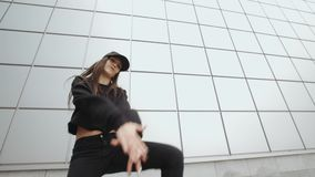 Woman dancer performs modern hip-hop dance, contemporary freestyle in the street, urban environment