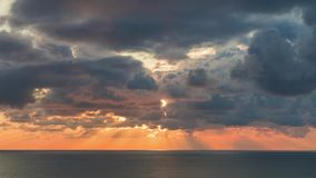 7b5727f1e34 Clouds crossing sky over the sea horizon at sunset with sun rays emerge  through the storm