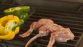 High quality video of grilled steaks in real slow motion, the process of cooking lamb or veal on bone and vegetables. Three beautiful even pieces of steak on stock images