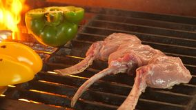 High quality video of grilled steaks in real slow motion, the process of cooking mutton or veal on a bone and vegetables. Through three beautiful even pieces stock images