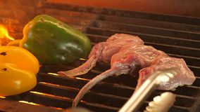 High quality video of grilled steaks in real slow motion, the process of cooking mutton or veal on a bone and vegetables. Through three beautiful even pieces royalty free stock photography