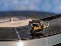 High quality vinyl record deck and tone arm. Side view of a playing vinyl record on vintage hi-fi stereo turntable with tonearm and cartridge in tracks of the LP Royalty Free Stock Image