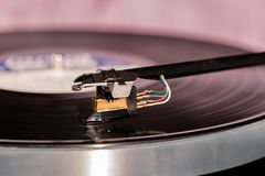 High quality vinyl record deck and tone arm. Side view of a playing vinyl record on vintage hi-fi stereo turntable with tonearm and cartridge in tracks of the LP Stock Photography