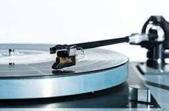 High quality vinyl record deck and tone arm. Side view of a playing vinyl record on vintage hi-fi stereo turntable with tonearm and cartridge in tracks of the LP Stock Image