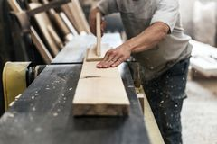 High quality wood concept. Cropped photo of mature cabinetmaker or handyman make furniture in garage or workroom using woodworking royalty free stock image