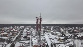 High radio tower with television and mobile antennas in winter village aerial view. Drone view communication tower with. Antennas for radio and mobile wave stock footage