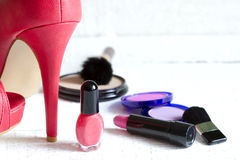 High red heels and set of cosmetics. Abstract on white planks Royalty Free Stock Photography