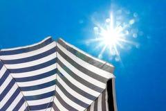 High resolution beach umbrella on blue sky background Royalty Free Stock Photos