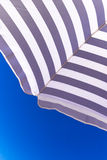 High resolution beach umbrella on blue sky background Royalty Free Stock Photos