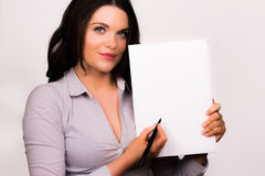 Beautiful young female presenting with a pen and paper Stock Photo