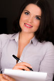 Beautiful young female presenting with a pen and paper. A high resolution image of a beautiful young female presenting with a pen and paper Stock Images