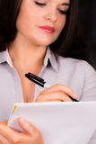 Beautiful young female presenting with a pen and paper Royalty Free Stock Image