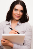 Beautiful young female presenting with a pen and paper. A high resolution image of a beautiful young female presenting with a pen and paper Stock Photography