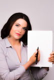 Beautiful young female presenting with a pen and paper Royalty Free Stock Photos