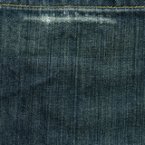 Denim Fabric Texture - Worn Imperial Blue XXXXL. High resolution scan of blue denim fabric with a wear-out mark and stitch crossing Stock Photos