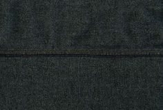 Denim Fabric Texture - Dark Gray With Seams. High resolution scan of dark gray / black denim fabric, with two horizontal yellow seams crossing Stock Image