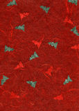 Rice Paper Texture - Christmas Red. High resolution scan of red rice paper with a pattern of green pine trees decorating its surface Royalty Free Stock Image