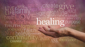 High Resonance Healing Words. Healer's outstretched open hand surrounded by random wise healing words on a rustic stone effect background Royalty Free Stock Photos