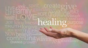 High Resonance Healing Words on pastel background. Healer's outstretched open hand surrounded by random wise healing words on a pale rustic stone effect Stock Photography