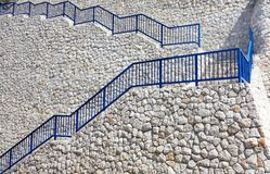 High White Rock Retaining Wall and Blue Stair Rails, Croatia. A high retaining wall, with steep staps, constructed from tight and close fitting white rocks, with royalty free stock image
