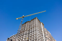 High-rise apartment building and tower crane against dark blue s. High-rise apartment building and building crane against dark blue sky background stock images