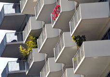 High rise balconies with plants. A corner of a high rise with repeating  balconies, some of them having colorful plants Stock Photo