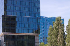 High-rise building with a blue glass facade against the sky and Stock Photography