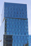 High-rise building with a blue glass facade against the sky Stock Images