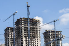 High-rise building at a construction site. Surrounded by construction cranes Royalty Free Stock Photography