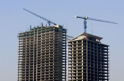 High-rise Building Construction. High-rise building under construction, cranes against blue sky Stock Image