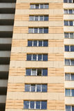 High rise building facade, eight floors, dark yellow wall and glass windows. Royalty Free Stock Photos
