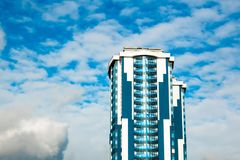 High-rise building with a glass facade against a bright blue sky with figured clouds.  Royalty Free Stock Photos