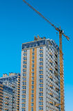High-rise building, and standing next to the tower crane. High-rise building in light blue and yellow tower crane standing next Royalty Free Stock Photos
