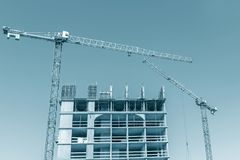 High-rise building under construction against blue sky. High-rise building under construction. building site with cranes against blue sky royalty free stock photos