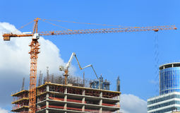 High-rise building under construction with crane and concrete pump. Stock Image