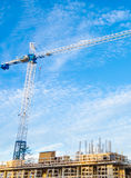 High-rise building under construction. The site with crane against blue sky with white clouds Royalty Free Stock Photography