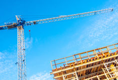 High-rise building under construction. The site with crane against blue sky with white clouds Royalty Free Stock Photo