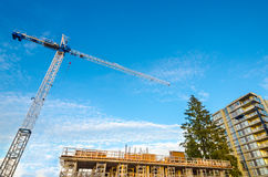 High-rise building under construction. The site with crane against blue sky with white clouds Stock Image