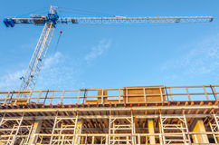 High-rise building under construction. The site with crane against blue sky with white clouds Royalty Free Stock Image