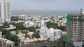 Dark clouds hover over the Landscape of Mumbai Suburb on a rainy day. High rise buildings along the sea coast in the western suburbs Versova, Andheri of Bombay stock images