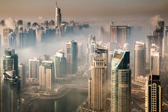 High-rise buildings and fog clouds in urban cityscape. Dense fog engulfs Dubai Marina, United Arab Emirates Royalty Free Stock Photos