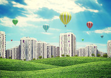 High-rise buildings over green hills, air balloons Stock Images