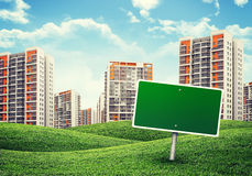 High-rise buildings over green hills and billboard Royalty Free Stock Photos