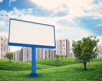High-rise buildings over green hills and billboard Stock Photos