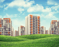 High-rise buildings over green hills Stock Photography