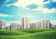 High-rise buildings over green hills Royalty Free Stock Photo