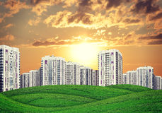 High-rise buildings over green hills Stock Photo