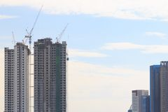 High rise buildings under construction. High rise buildings under construction, on blue sky background Royalty Free Stock Photo